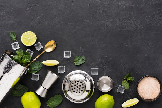 Bovenaanzicht van cocktail essentials met munt en limoen