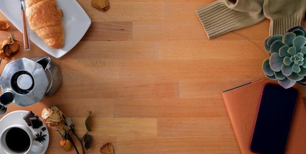 Bovenaanzicht van comfortabele werkplek met kantoorbenodigdheden en ontbijt op houten tafel
