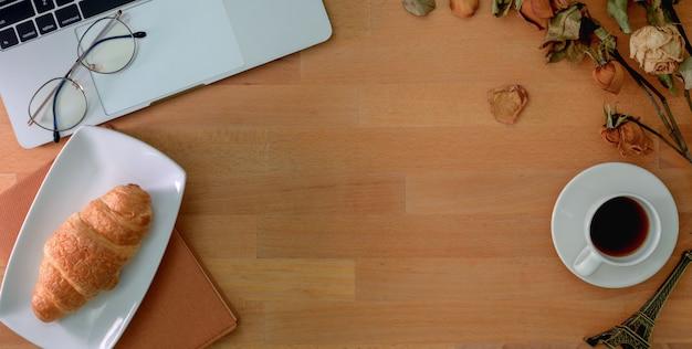 Bovenaanzicht van comfortabele werkplek met laptopcomputer, kantoorbenodigdheden en ontbijt op houten tafel