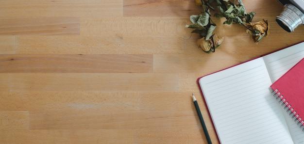 Bovenaanzicht van comfortabele werkplek met open notebook- en kantoorbenodigdheden
