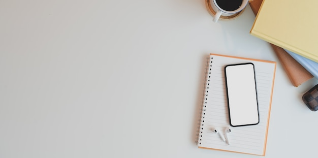 Bovenaanzicht van comfortabele werkruimte met leeg scherm smartphone op wit houten bureau met kantoorbenodigdheden