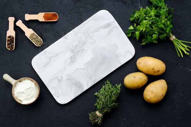 Bovenaanzicht van compositie met marmeren serveerplank en ingrediënten