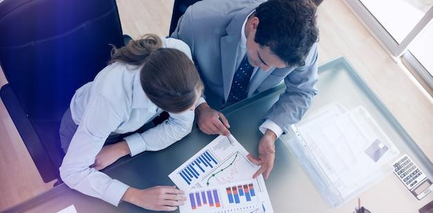 Bovenaanzicht van consultant die gegevens analyseert met haar klant