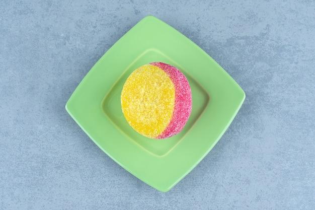 Bovenaanzicht van cookie op perzikvorm over groene plaat.