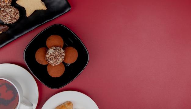 Bovenaanzicht van cookies in plaat met kopje thee op rode achtergrond met kopie ruimte