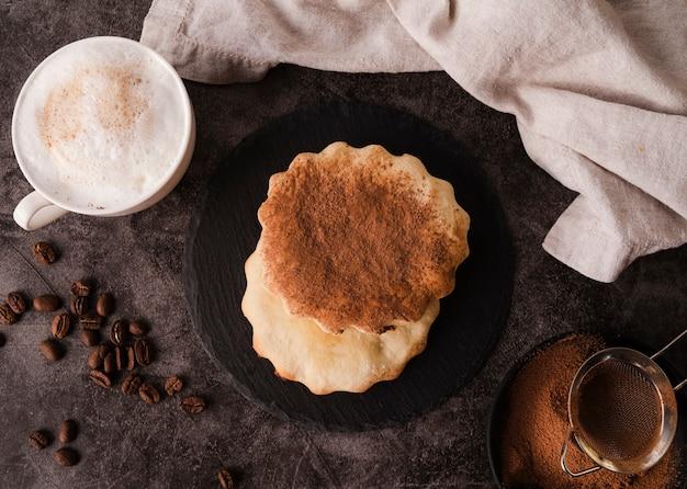 Bovenaanzicht van cookies met cacaopoeder bovenop en mok
