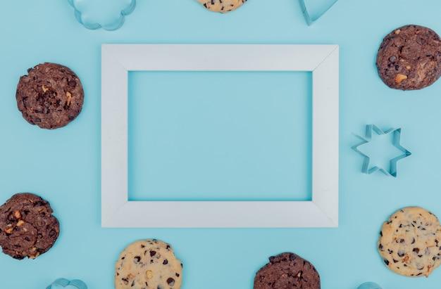 Bovenaanzicht van cookies rond frame op blauwe achtergrond met kopie ruimte
