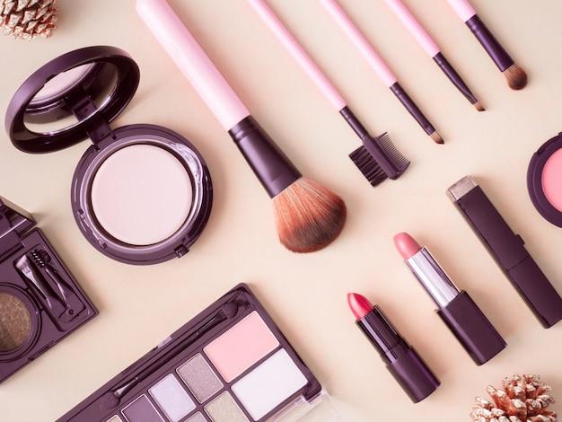 Bovenaanzicht van cosmetica concept met lippenstift, make-up producten, oogschaduw palet, poeder op crème kleurentabel.