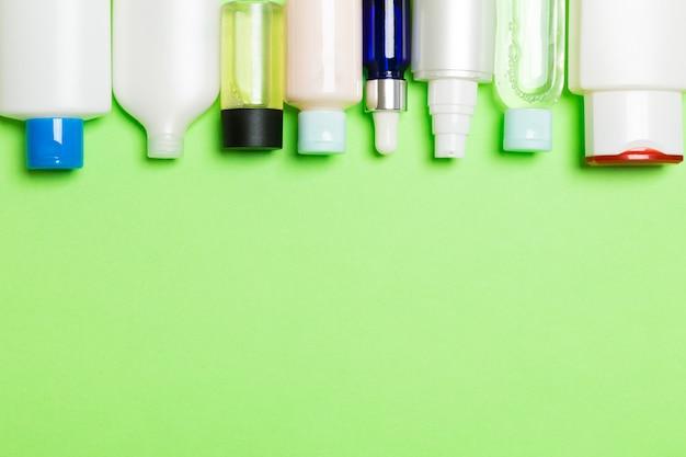 Bovenaanzicht van cosmetica flessen op groene achtergrond. huidverzorging concept
