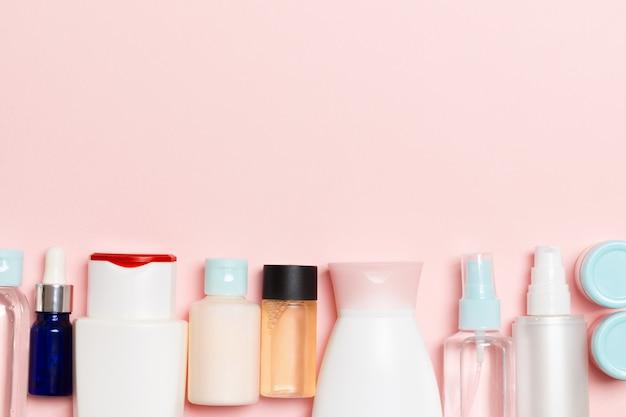 Bovenaanzicht van cosmetica flessen op roze achtergrond