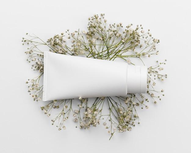 Bovenaanzicht van cosmetische fles op bloemen