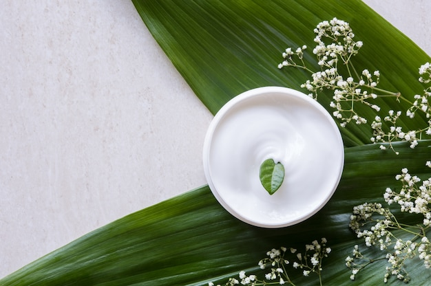 Bovenaanzicht van cosmetische lotion met bloemen en groen blad.