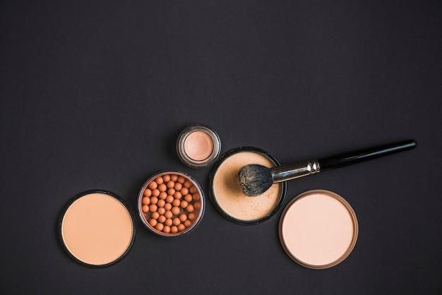 Bovenaanzicht van cosmetische producten en make-up borstel op zwarte achtergrond