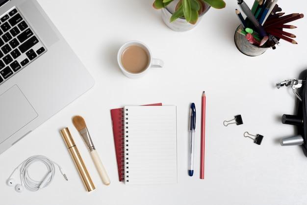 Bovenaanzicht van cosmetische producten; kantoorartikelen; laptop en een koffiekopje met planten op een bureau