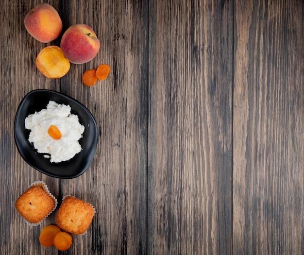 Bovenaanzicht van cottage cheese in een zwarte kom met muffins verse perziken en gedroogde abrikozen op rustieke houten tafel met kopie ruimte