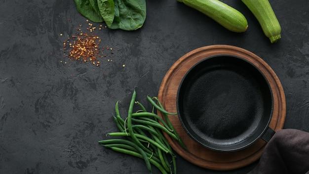 Bovenaanzicht van courgette, spinazieblaadjes, kruiden en sperziebonen rond lege kookpan op donkere tafel