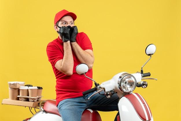 Bovenaanzicht van courier man draagt rode blouse en muts handschoenen in medisch masker leveren bestelling zittend op scooter kijken naar iets met bang gelaatsuitdrukking