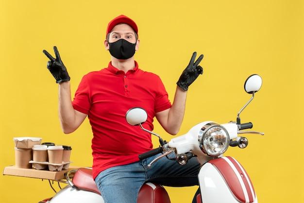 Bovenaanzicht van courier man dragen rode blouse en muts handschoenen in medische masker leveren bestelling zittend op scooter overwinning gebaar maken