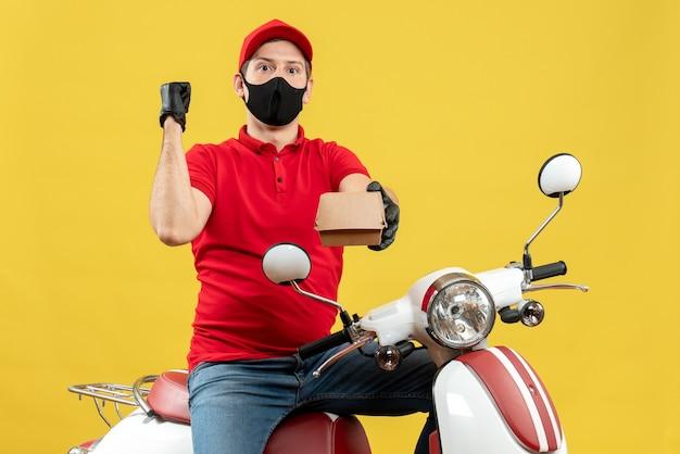 Bovenaanzicht van courier man met rode blouse en hoed handschoenen in medische masker zittend op scooter holding order terug te wijzen