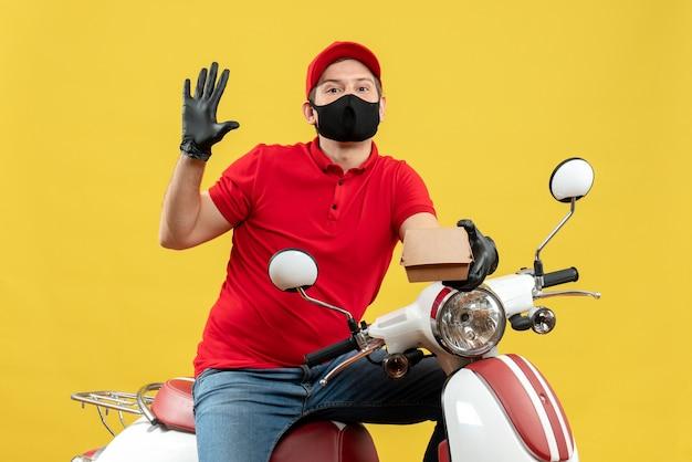 Bovenaanzicht van courier man met rode blouse en muts handschoenen in medische masker zittend op scooter holding order trots gevoel