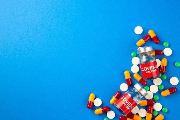 Bovenaanzicht van covid-vaccin in medische ampullen capsules pillen op blauwe achtergrond met vrije ruimte