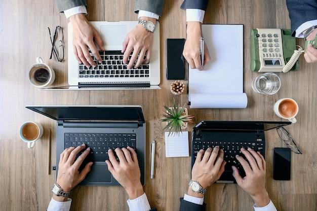 Bovenaanzicht van coworking mensen werken aan laptops en papieren documenten.