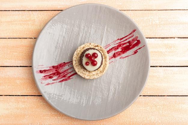 Bovenaanzicht van cracker en cake met veenbessen bovenop in paarse plaat