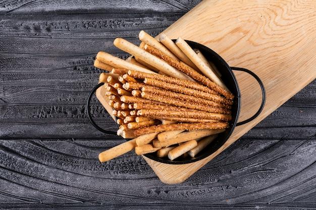Bovenaanzicht van crackers in zwarte pan en houten snijplank op donkere horizontaal