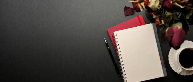Bovenaanzicht van creatieve plat lag werkruimte met notebooks, gedroogde rozen, koffiekopje en kopie ruimte op zwarte tafel