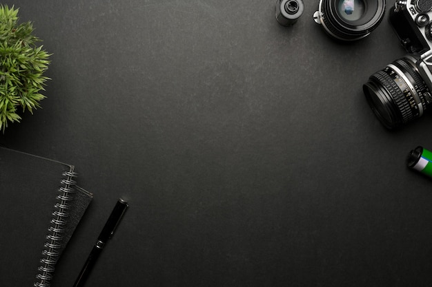 Bovenaanzicht van creatieve plat lag zwarte tafel met camerabriefpapier en kopie ruimte