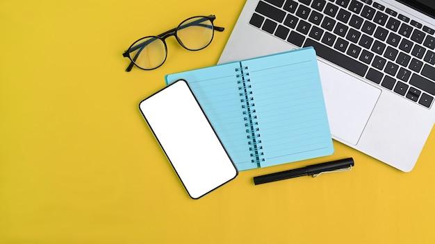Bovenaanzicht van creatieve werkruimte met computer laptop, notebook, smartphone en bril op gele achtergrond.
