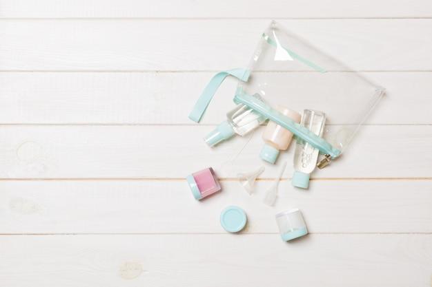 Bovenaanzicht van crème containers met wattenschijfjes in overnachting tas