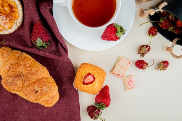 Bovenaanzicht van crescent roll knapperig knäckebröd op doek en kopje thee met aardbeien en cupcake met witte chocolade op witte ondergrond