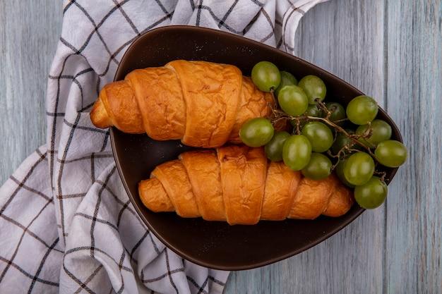 Bovenaanzicht van croissants en druivenmost in kom op geruite doek op houten achtergrond