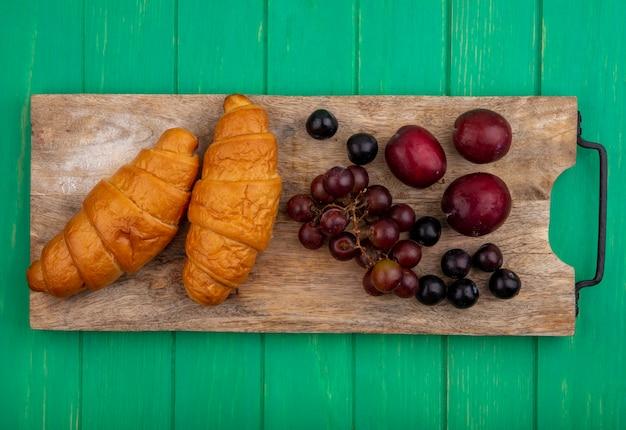 Bovenaanzicht van croissants en druivenmost pluots sleedoorn bessen op snijplank op groene achtergrond