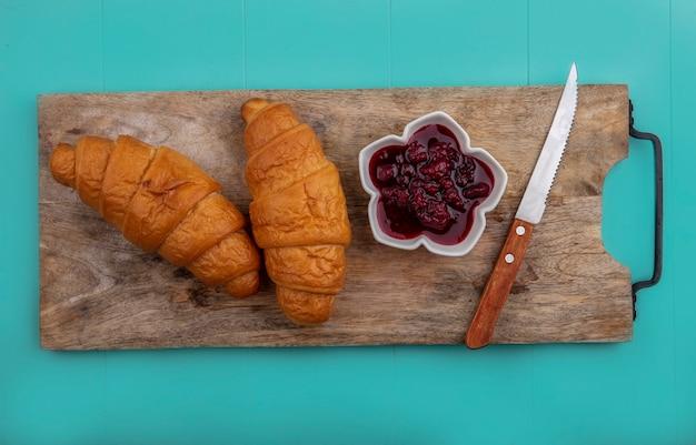 Bovenaanzicht van croissants en frambozenjam met mes op snijplank op blauwe achtergrond