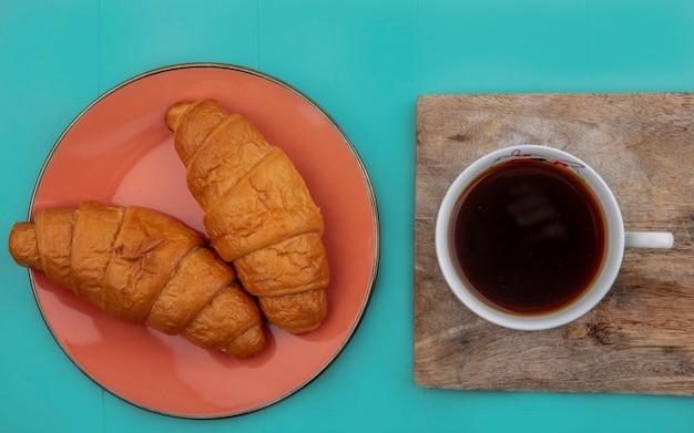 Bovenaanzicht van croissants in plaat en kopje thee op snijplank op blauwe achtergrond