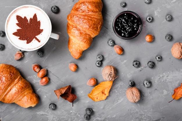 Bovenaanzicht van croissants, jam en koffie ontbijt