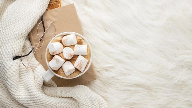 Bovenaanzicht van cup met warme marshmallows en glazen op boek