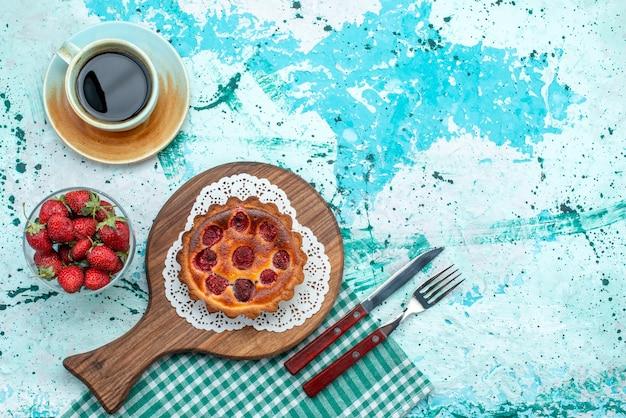Bovenaanzicht van cupcake met aardbeien naast lepel en vork en americano