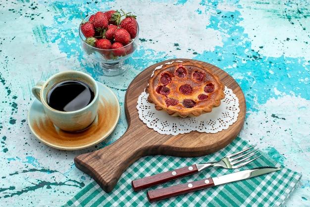 Bovenaanzicht van cupcake met gebakken oppervlak naast americano en aardbeien
