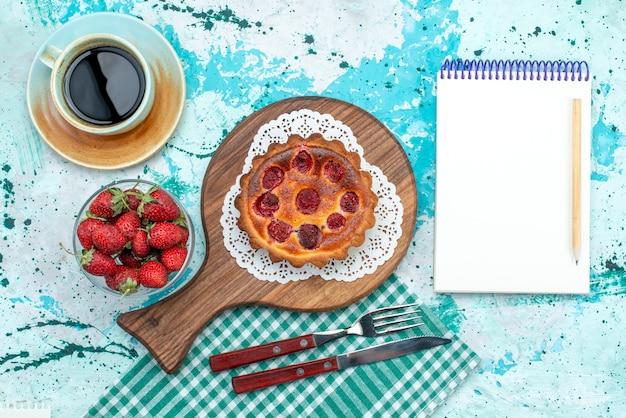 Bovenaanzicht van cupcake met gebakken oppervlak naast notebook en americano