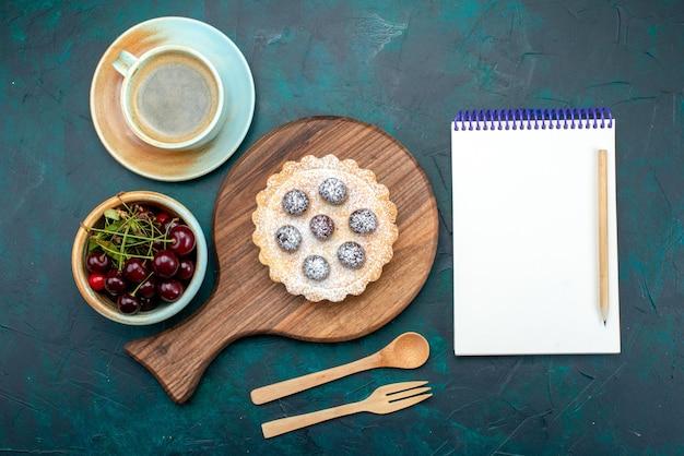 Bovenaanzicht van cupcake met kersen en suikerpoeder naast hete koffie en notitieboekje