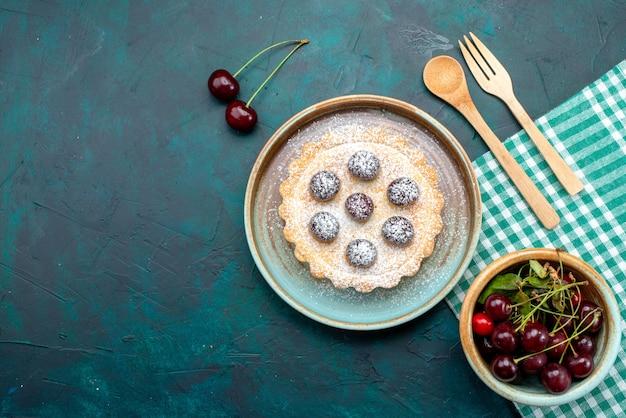 Bovenaanzicht van cupcake met lekkere kersen en suikerpoeder naast kersenplaat