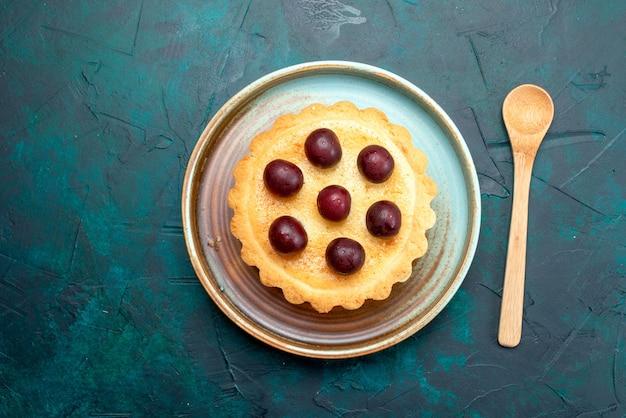 Bovenaanzicht van cupcake met zure kersen naast lepel op donkerblauw,