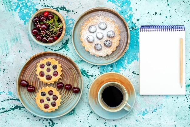 Bovenaanzicht van cupcakes met alle kersen naast kopje americano en notebook