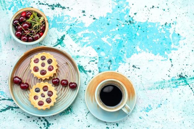 Bovenaanzicht van cupcakes met kleine kersen naast americano op lichtblauw,