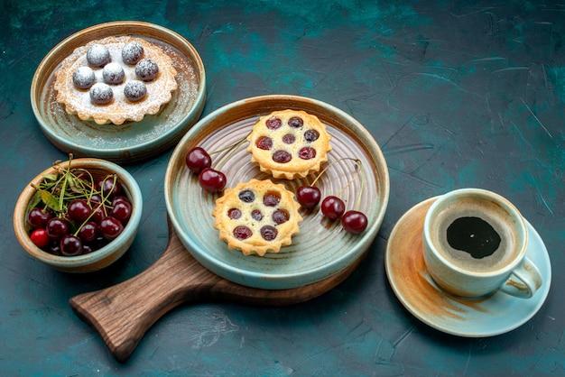 Bovenaanzicht van cupcakes met ronde kersen naast americano
