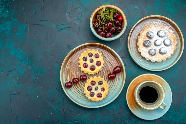 Bovenaanzicht van cupcakes met suikerpoeder en verse kersen in de buurt van warme americano en kersenplaat