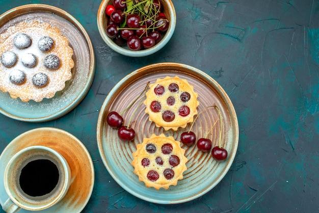 Bovenaanzicht van cupcakes met zure kersen en kopje koffie op blauw,